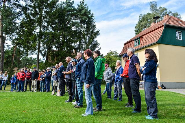 Viele Vereinsmitglieder versammelt am Flaggenmast