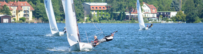 Ein Segler am Wind im Flying Dutchman (FD) beim ausreiten im Trapez, zusätzlich wird eine Hand über den Kopf gestreckt