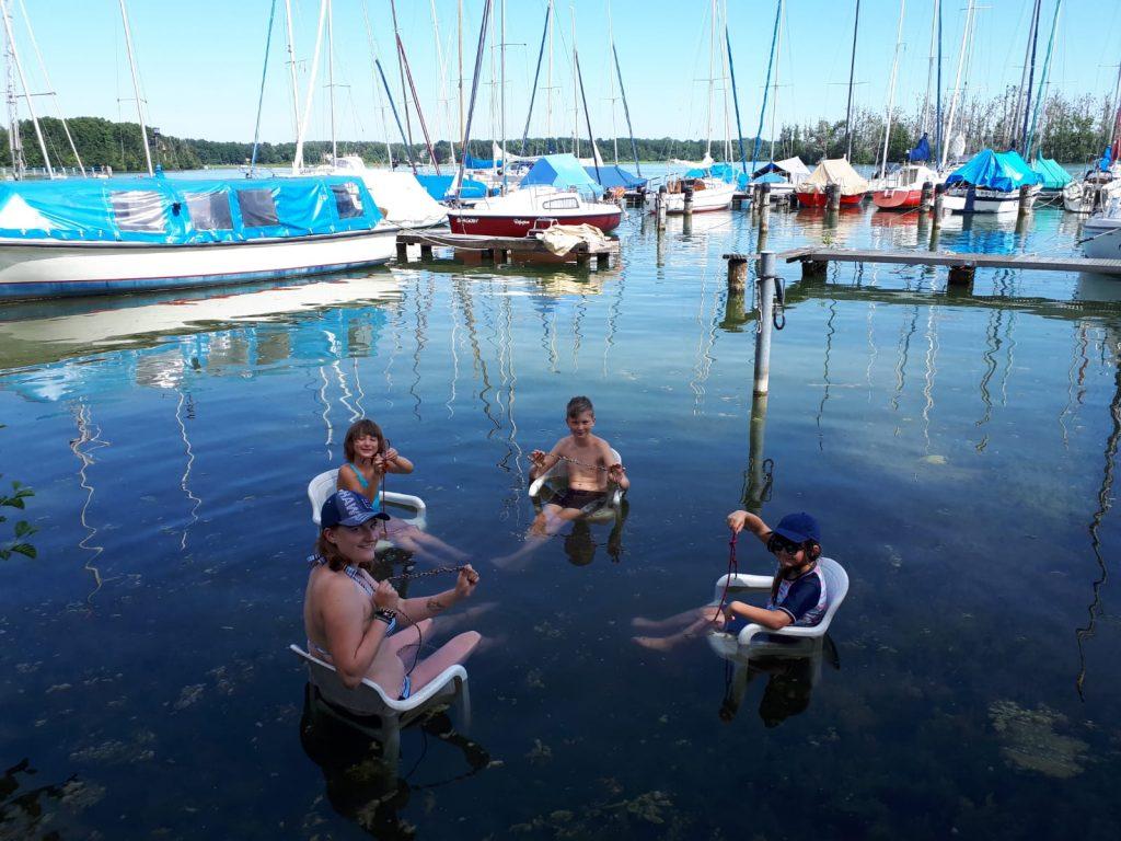Die Jugend sitzt zur Abkühlung im Wasser