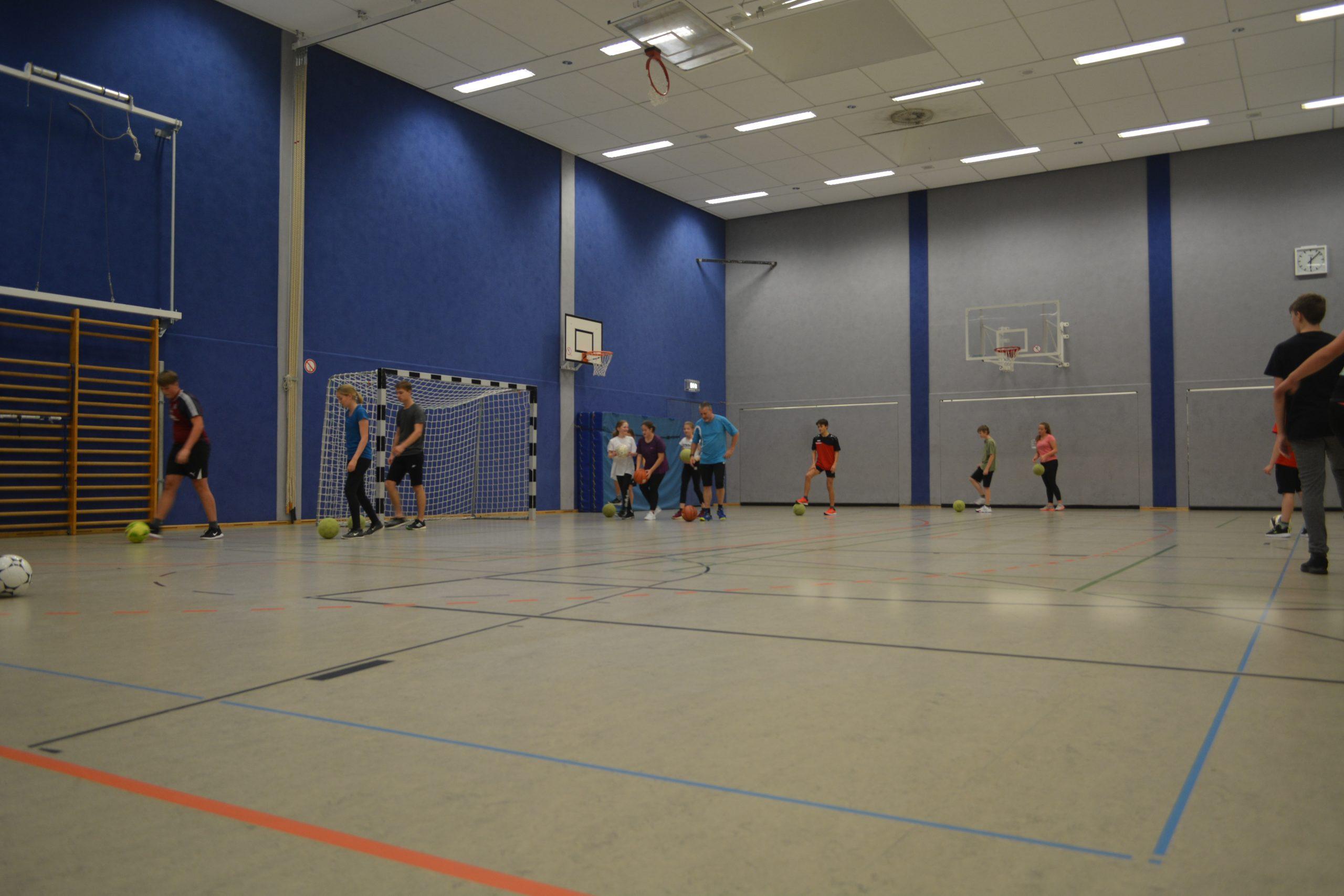 Kinder in der Sporthalle, machen Übungen mit Fußbällen